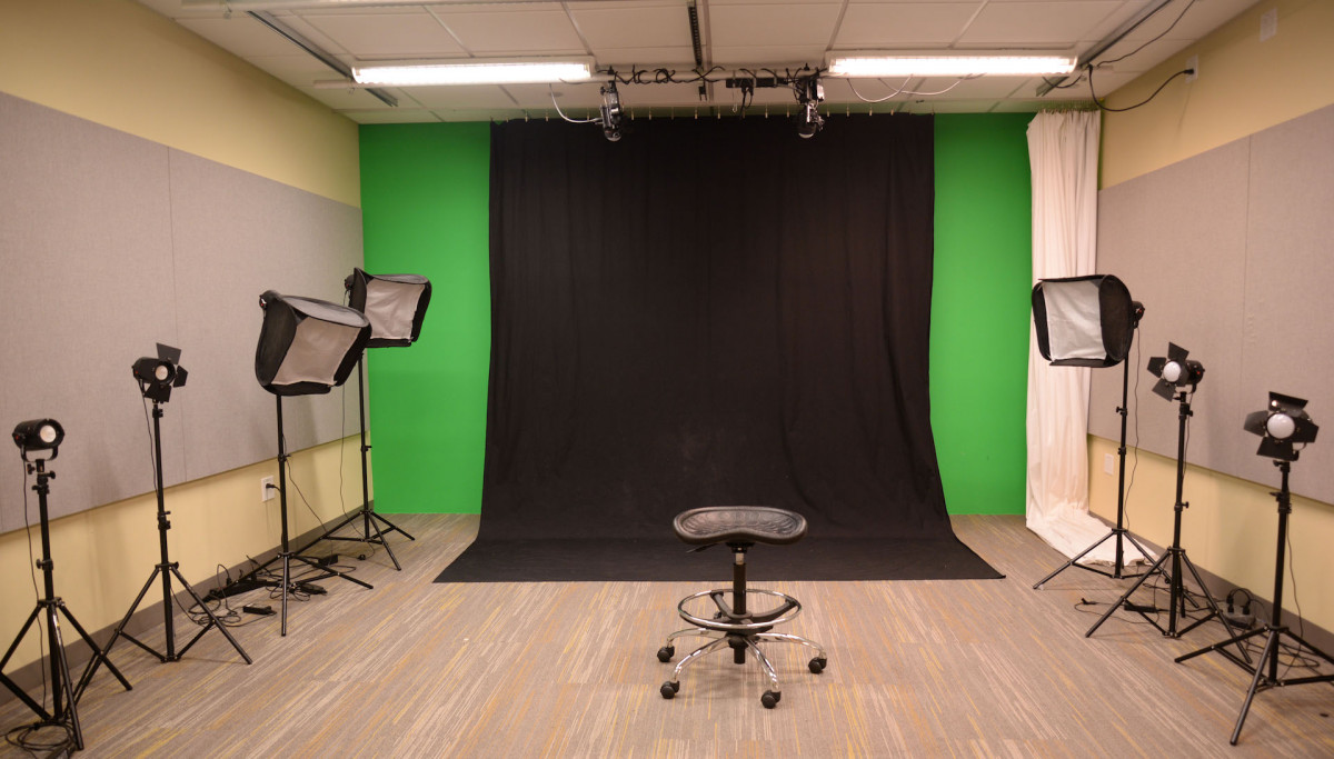 DMC video studio has 2 ceiling mounted lights, 7 lights on the floor and a black curtain and a white curtain.