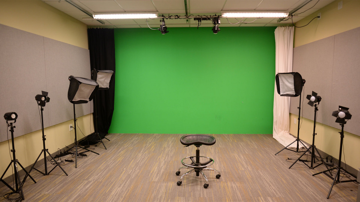 DMC video studio has 2 ceiling mounted lights, 7 lights on the floor and a green wall.